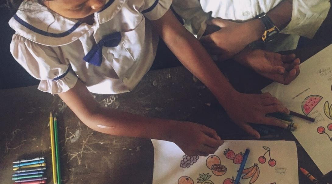 カンボジアの学校で塗り絵を通して果物の英単語を学ぶ子供たち